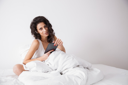internet surfing: Brunette long hair woman on white bed in soft morning light under the duvet with a tablet computer. Concept of happy family living, relaxation, comfort, fun, internet surfing and communicating Stock Photo