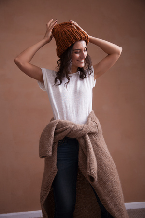 Young smiling woman in knitted sweater and hat. Concept of freelance creative working and happy living