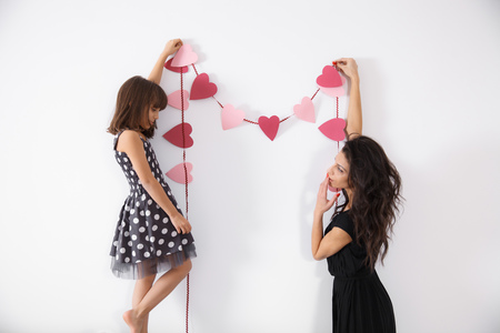 holidays: Mothher and daughter decorating the house with heart shaped garland. Concept of family values, happy living, celebrating the holidays, preparing for valentines day