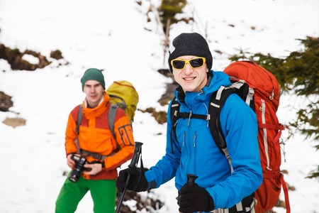 Two male hikers with backpacks in winter mountains passing to camera. Concept of success living and free traveling, active leisure, health care and well being.