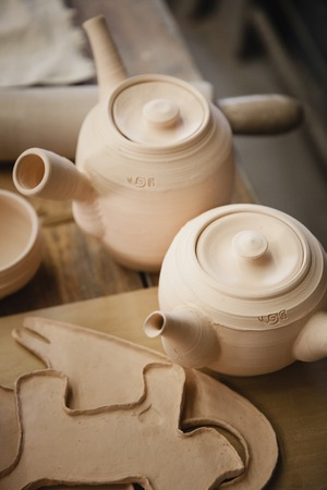 fireclay: Roasted ceramimc teapots without glaze. Top view, closeup. Art and business, hobby and freelance working concept. Stock Photo