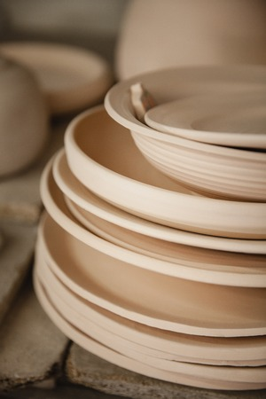 fireclay: Roasted ceramimc plates without glaze. Front view, closeup. Art and business, hobby and freelance working concept. Stock Photo