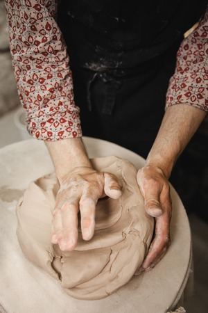 fireclay: Adult male potter master mashing the clay on table. Front view, closeup, hands only. Art and business, hobby and freelance working concept.