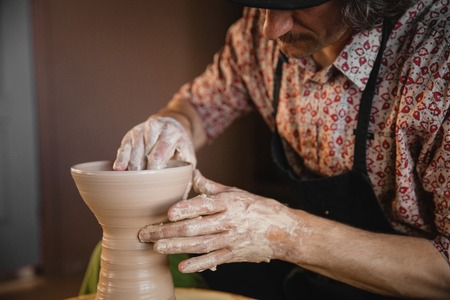 bisquit: Adult male potter master creating new ceramic bowl on pottery wheel. Front view, closeup, focus on hands. Art and business, hobby and freelance working concept. Stock Photo