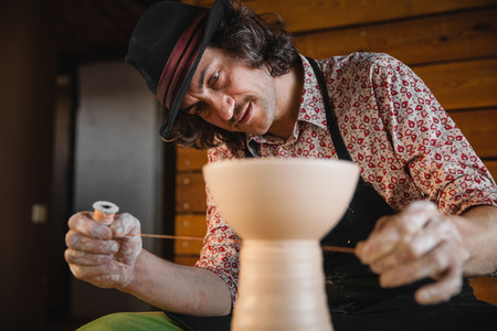 Adult male potter master creating new ceramic bowl on pottery wheel. Front view, closeup portrait. Art and business, hobby and freelance working concept. Stock Photo