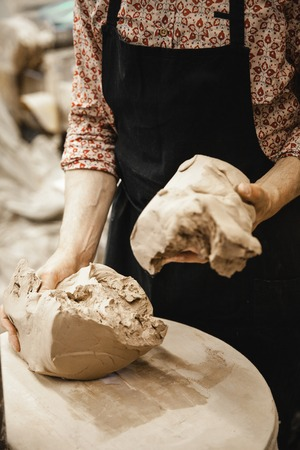 fireclay: Adult male potter master preparing the clay on table. Front view, closeup, hands only, unrecognizable. Art and business, hobby and freelance working concept. Stock Photo
