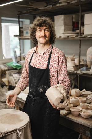 fireclay: Adult male potter master mashing the clay on table. Front view, closeup portrait. Art and business, hobby and freelance working concept.