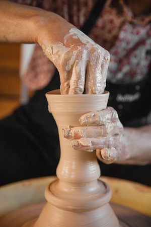 fireclay: Adult male potter master creating new ceramic bowl on pottery wheel. Front view, closeup, focus on hands, unrecognizable. Art and business, hobby and freelance working concept.