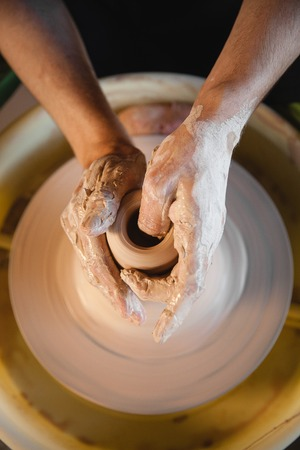 fireclay: Adult male potter master creating new ceramic bowl on pottery wheel. Top view, closeup, focus on hands, unrecognizable. Art and business, hobby and freelance working concept. Stock Photo