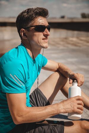 Adult male athlete drinking water against office buildings after urban running. Concept of hard working and active living, freelance, remote business, healthcare and wellbeing Stock Photo