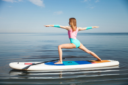 Young woman doing yoga on sup board with paddle. Mediatative pose, side view - concept of harmony with the nature, free and healthy living, freelance, remote business.