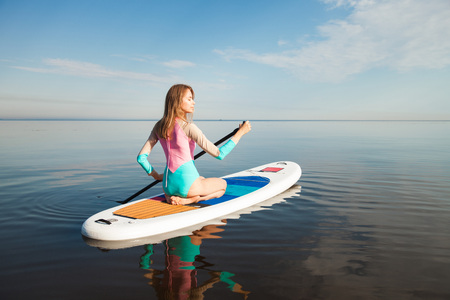 sup: Young woman paddling on sup board with paddle. Sitting pose - concept of harmony with the nature, free and healthy living, freelance, remote business. Stock Photo