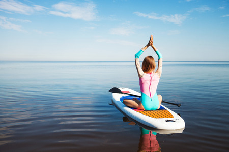 Unrecognizable young woman doing yoga on sup board with paddle. Mediatative pose, back view - concept of harmony with the nature, free and healthy living, freelance, remote business.