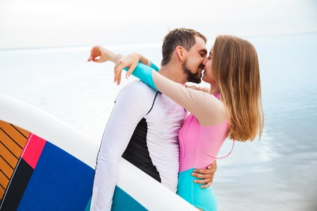 sup: Young couple hugging and kissing on the beach with sup board. Side view closeup - concept of harmony with the nature, free and healthy living, freelance, remote business.
