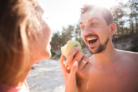Young couple bitting green apple on the beach. Front view closeup - concept of harmony with the nature, free and healthy living, freelance, remote business.