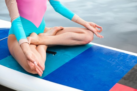 Unrecognizable young woman doing yoga on sup board with paddle. Meditative pose, front view - concept of harmony with the nature, free and healthy living, freelance, remote business.