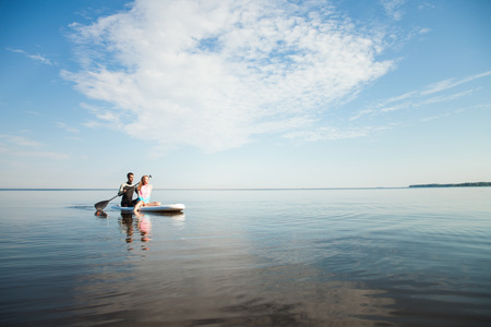 Young couple paddling on sup board with paddle. Sitting poses, side view - concept of harmony with the nature, free and healthy living, freelance, remote business.
