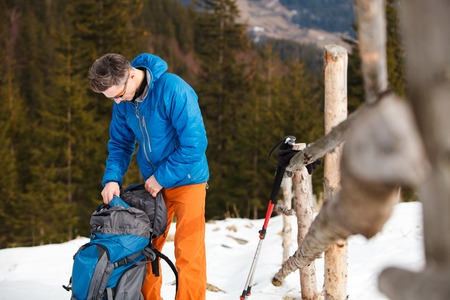 Hiker packing backpack closeup on mountain snow. Concept of success living and free traveling, active leisure, health care and well being.