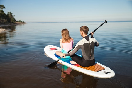 sup: Young couple paddling on sup board with paddle along the beach. Sitting poses, back view - concept of harmony with the nature, free and healthy living, freelance, remote business.
