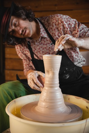 fireclay: Adult male potter master creating new ceramic pot on pottery wheel. Front view, closeup portrait. Art and business, hobby and freelance working concept.