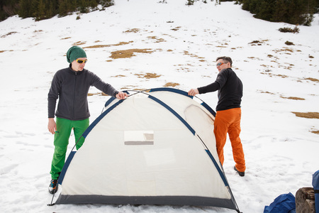 Two hikers in winter mountains installing tent. Concept of success living and free traveling, active leisure, health care and well being. Stock Photo
