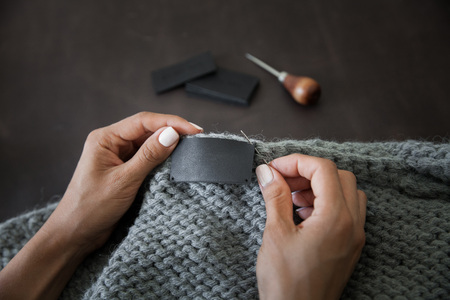 sew tags: Woman sewing the blank genuine leather lable on knitted clothing. Empty tag for your logo. Unrecognizable, closeup, hands only, mockup.