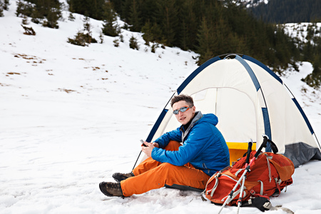 Mountain hiker in advanced base camp with tent talking on smartphone. Concept of success living and free traveling, active leisure, health care and well being.