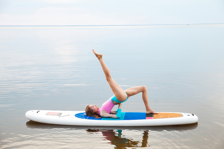 Young woman doing yoga on sup board with paddle. Meditative pose, side view - concept of harmony with the nature, free and healthy living, freelance, remote business. Stock Photo