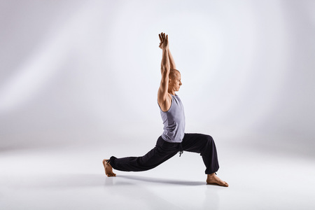 cognicion: Sporty middle age man doing yoga practice isolated on white background - concept of healthy life and natural balance between physical and mental evolution Foto de archivo