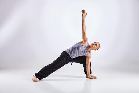cognicion: Deportivo hombre de mediana edad la práctica haciendo yoga aislado sobre fondo blanco - concepto de vida sana y el equilibrio natural entre la evolución física y mental Foto de archivo