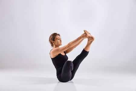 Sporty middle age woman doing yoga practice isolated on white background - concept of healthy life and natural balance between physical and mental evolution Stock Photo