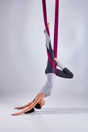 Young woman practices aerial different inversion anti-gravity yoga with a hammock in a white studio. Concept of a mental and physical health an harmony living Reklamní fotografie - 66139301