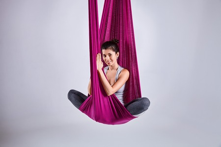 Young woman practices aerial different inversion anti-gravity yoga with a hammock in a white studio. Concept of a mental and physical health an harmony living