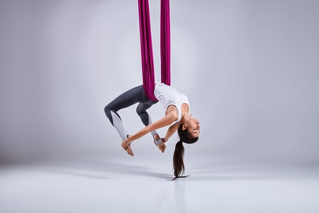 concentration: Young woman practices aerial different inversion anti-gravity yoga with a hammock in a white studio. Concept of a mental and physical health an harmony living
