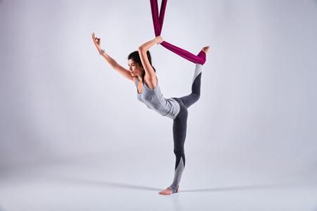 inversion: Young woman practices aerial different inversion anti-gravity yoga with a hammock in a white studio. Concept of a mental and physical health and harmony living Stock Photo