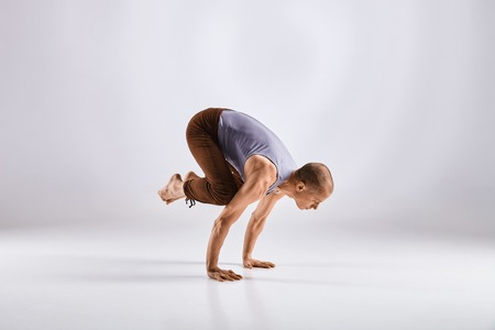 Sporty middle age man doing yoga practice isolated on white background - concept of healthy life and natural balance between physical and mental evolution Stock Photo