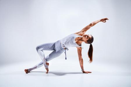 ホワイト バック グラウンド - 健康的な生活と精神的な開発と体の自然なバランスの概念に分離のヨガの練習を行うスポーティな若い女性
