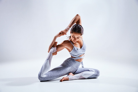 Sporty young woman doing yoga practice isolated on white background - concept of healthy life and natural balance between body and mental development Stock Photo