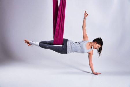 Young woman practices aerial different inversion anti-gravity yoga with a hammock in a white studio. Concept of a mental and physical health and harmony living Stok Fotoğraf