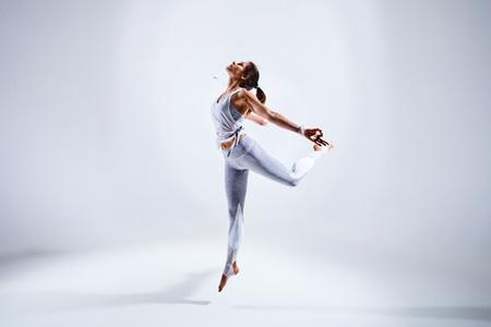 Sportieve jonge vrouw doet yoga praktijk geïsoleerd op witte achtergrond - concept van gezond leven en natuurlijke balans tussen lichaam en mentale ontwikkeling Stockfoto
