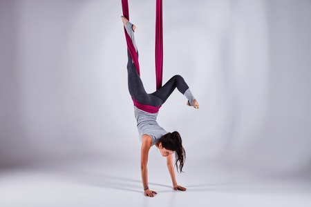 Young woman practices aerial different inversion anti-gravity yoga with a hammock in a white studio. Concept of a mental and physical health and harmony living Reklamní fotografie - 77510497