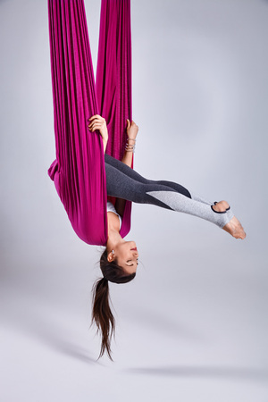 Young woman practices aerial different inversion anti-gravity yoga with a hammock in a white studio. Concept of a mental and physical health and harmony living Фото со стока