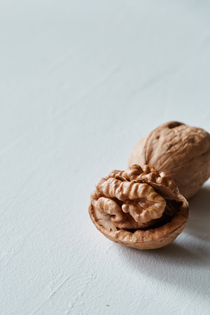 Walnut and kernel on a white rustic backdrop. Healthy raw snack or organic vegetarian meal ingredients.