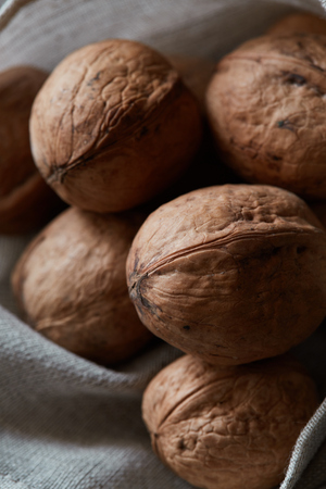 Close-up crop of walnuts on a rough fabric sack. Healthy raw snack or organic vegetarian meal ingredients. Stock Photo