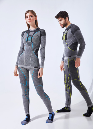 Young couple man and woman in hot sports thermal underwear for downhill skiing and extreme winter hiking - studio isolated image on white background