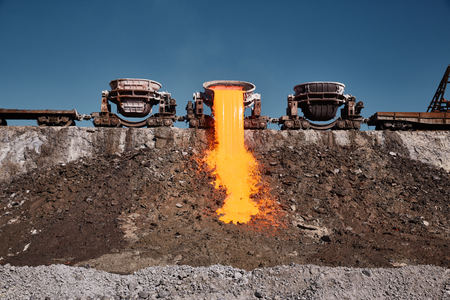 crucible: The molten slag is poured from a crucible mounted on a railway platform. A stream of molten slag.