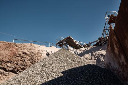 Breek-, maal-, sorteer- en transportlijnen op slakkenstortplaats. Zwaar industrieel metallurgisch mistig landschap met bouwmachines Stockfoto