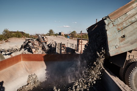 Crushing, grinding, sorting and transportation lines on slag dump. Grinders bunker loading from tipper truck Stock Photo