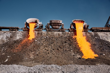 The molten slag is poured from a crucible mounted on a railway platform. A stream of molten slag.