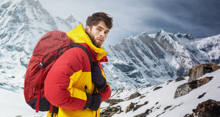 Handsome mountaineer in winter clothes with hiking equipment standing against astonishing snowy rocky landscape background